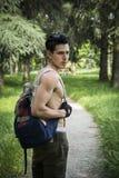 El caminar descamisado del hombre joven al aire libre con la mochila en hombro Imagen de archivo libre de regalías