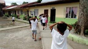 El caminar elemental de los alumnos, cubriendo sus cabezas como les enseñan a comportarse durante la situación del terremoto del  almacen de video