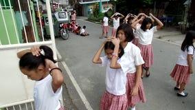 El caminar elemental de los alumnos, cubriendo sus cabezas como les enseñan a comportarse durante la situación del terremoto del  metrajes