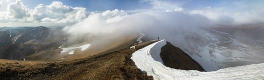 El caminar en canto nevoso de la montaña Imágenes de archivo libres de regalías