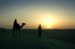 El caminar en el desierto del Sáhara, en la luz de la puesta del sol Fotos de archivo