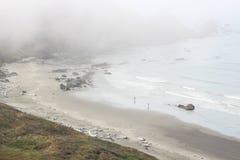 El caminar en la playa en la niebla Imagen de archivo