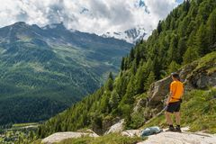 El caminar en las montañas italianas Caminante con la mochila, mirada en el panorama desde arriba fotografía de archivo libre de regalías