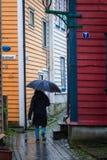 El caminar en lluvia a través de las calles estrechas en la ciudad vieja de Bergen Imagen de archivo