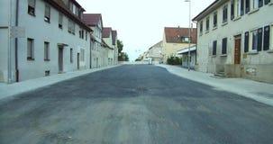 El caminar en el medio de la pequeña ciudad del camino en la calle de Europa Alemania con el camino del blacktop almacen de metraje de vídeo
