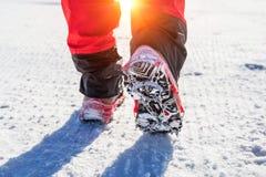 El caminar en nieve con los zapatos de la nieve y los puntos del zapato en invierno Foto de archivo