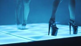 El caminar en tacones altos mientras que danza de poste en club de noche