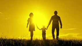 El caminar feliz de la familia, celebrando las manos en la puesta del sol