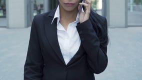 El caminar femenino del agente secreto con confianza, recibiendo instrucciones en el teléfono móvil metrajes