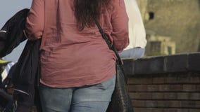 El caminar femenino rechoncho en calle desordenada de la ropa abajo el día soleado, cámara lenta almacen de metraje de vídeo