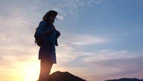 El caminar femenino turístico del caminante activo rodeado por la alta montaña al ángulo bajo de la puesta del sol almacen de metraje de vídeo