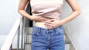 El caminar infeliz de la chica joven se encrespa para arriba con dolor de estómago porque dolor menstrual en la escalera en la pr metrajes