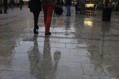 El caminar a lo largo de la calle mojada del pavimento Lluvia en la ciudad Fotos de archivo libres de regalías