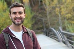 El caminar masculino sonriente a través de un puente Fotos de archivo