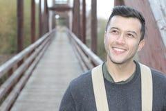 El caminar masculino sonriente a través de un puente Imagen de archivo