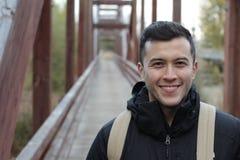 El caminar masculino sonriente a través de un puente Fotos de archivo libres de regalías