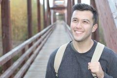 El caminar masculino sonriente a través de un puente Imagen de archivo libre de regalías