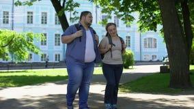 El caminar masculino y femenino del estudiante en el parque del campus, ligando el fecha, pares gordos almacen de metraje de vídeo