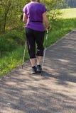 el caminar nórdico de la señora en parque de la primavera Imagen de archivo libre de regalías