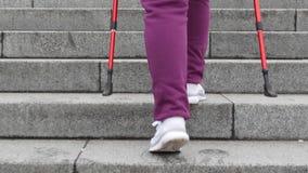 El caminar nórdico en las escaleras Mujer cauc?sica rechoncha joven que camina con los polos n?rdicos El cierre encima del lado t almacen de metraje de vídeo