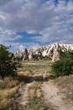 El caminar para abandonar el valle color de rosa de la piedra arenisca rocosa con las trogloditas Imagen de archivo libre de regalías