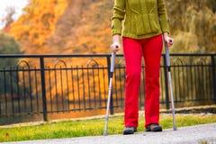 El caminar practicante de la mujer en las muletas Fotografía de archivo