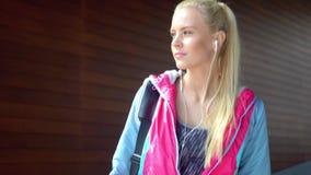El caminar rubio joven, atractivo y deportivo de la muchacha al aire libre con un bolso del deporte Atención sanitaria, aptitud y