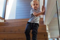 El caminar solo del niño pequeño abajo de las escaleras en casa Fotografía de archivo