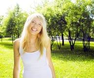 El caminar sonriente en parque verde, concepto de la muchacha rubia linda feliz de la gente de la forma de vida Imagenes de archivo