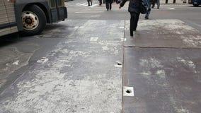 El caminar a través de la calle urbana con las cubiertas del hihole de la calle del torneado y del metal del autobús fotos de archivo
