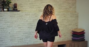El caminar a través de una señora rubia carismática del estudio aerobio ella saca la chaqueta de deporte y consigue lista para co metrajes