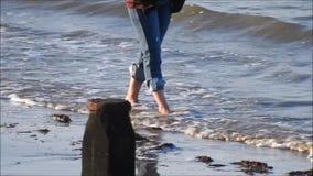 El caminar a través del océano descalzo de la playa de las ondas almacen de video