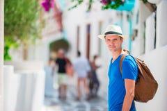 El caminar turístico caucásico a lo largo de las calles estrechas en Mykonos Muchacho urbano joven el vacaciones que explora la c Imágenes de archivo libres de regalías