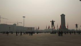 El caminar y contaminación de la gente de la Plaza de Tiananmen en el aire