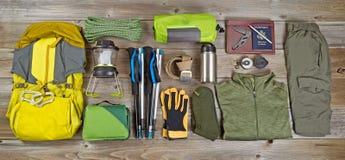 El caminar y equipo de acampada organizados en los tableros de madera rústicos Imágenes de archivo libres de regalías