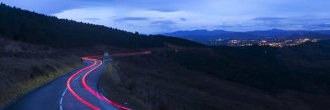 El camino con el coche se enciende en dirección de la ciudad de San Sebastián Imagen de archivo libre de regalías