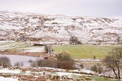 El camino congelado del invierno con nieve ligera en las colinas y el lago echan a un lado imágenes de archivo libres de regalías