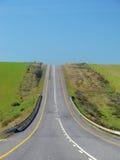 El camino a continuación - un camino de Stright encima de una colina Foto de archivo