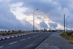 El camino curvado vacío de la alta manera de la carretera de asfalto se nubla y cielo en la puesta del sol Imagen de archivo