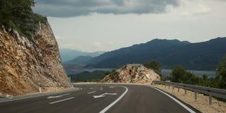 El camino da vuelta a una montaña Indicadores en el pavimento Montañas, lago y nubes en el fondo fotos de archivo