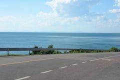 El camino de la carretera entra abajo en montañas con la opinión del mar en día soleado Imagen de archivo libre de regalías