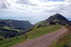 El camino de la grava va cuesta abajo al valle rural Imagen de archivo libre de regalías