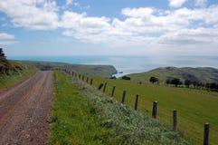El camino de la grava va cuesta abajo al valle rural Foto de archivo libre de regalías
