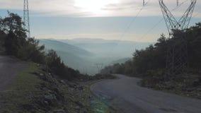El camino de la montaña con vueltas y curvas desciende entre las colinas con las líneas eléctricas de alto voltaje 4K almacen de video