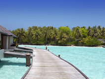 El camino de madera sobre el mar a la isla tropical Imágenes de archivo libres de regalías