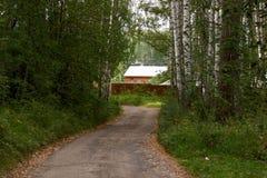 El camino del bosque está llevando a una casa sola Foto de archivo libre de regalías