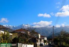 El camino del pueblo de montaña en la península de Peloponeso de Grecia con niebla nevada cubrió las montañas en el fondo jpg Foto de archivo libre de regalías