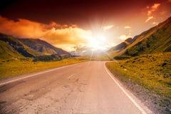 El camino en las montañas ajardina con puesta del sol brillante Fotos de archivo