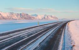 El camino en un día de invierno soleado a lo largo de las montañas coronadas de nieve Foto de archivo