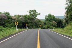 El camino, la calle, el camino de la avenida, el camino del campo y las señales de tráfico de la curva enderezan en Tailandia Imagenes de archivo